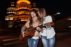 Nightlife girlfriends, girls with a guitar. Young people walk at night against the blurred city lights Stock Photos