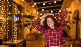 Nightlife, people and fun concept - Beautiful young woman poses near bright restaurant on the street at night royalty free stock images