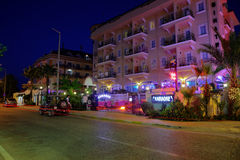 Nightlife in resort settlement, colorful lighting building facade of hotel. Camyuva village, Kemer, Antalya, Turkey - August 26, 2014: Night street in the royalty free stock photos