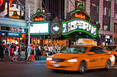 Nightlife on the streets of New York. With lots of people in the streets, in front of Hard Rock Cafe. A traditional well known yellow cab passes by Royalty Free Stock Photo