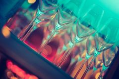 Nightlife: Wine glasses and colourful lights in a night club. Wine glasses in a night club, colourful lights in the blurry background nightlife atmosphere party stock image