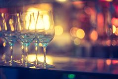 Nightlife: Wine glasses and colourful lights in a night club. Wine glasses in a night club, colourful lights in the blurry background nightlife atmosphere party stock photography