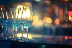 Nightlife: Wine glasses and colourful lights in a night club. Wine glasses in a night club, colourful lights in the blurry background nightlife atmosphere party stock photos