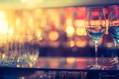 Nightlife: Wine glasses and colourful lights in a night club. Wine glasses in a night club, colourful lights in the blurry background nightlife atmosphere party royalty free stock image