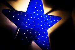 Nightlight in the shape of a star in the children`s room Stock Photos