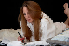 Nightly Journal. A woman writes in her diary while in bed royalty free stock photography