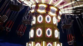 A nightly merry-go-round in the lights, rolls people around. HD, 1920x1080. Slow motion stock video footage