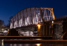 Nightly railroad bridge over stream in winter Royalty Free Stock Photography