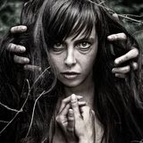 Nightmare and Halloween theme: portrait of scary girl witch in the woods Royalty Free Stock Photography