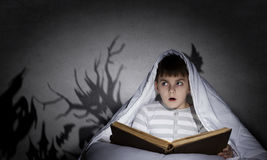 Nightmares of child. Little scared boy in bed under blanket with flashlight Royalty Free Stock Photography