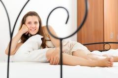 Nightrobe vestindo da menina que encontra-se na cama Foto de Stock Royalty Free