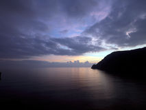 Nights falls with crescent moon and calm sea. Stock Photography