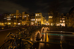 Nightscape avec les traînées légères des voitures et des bateaux croisant au-dessus des canaux d'Amsterdam images stock