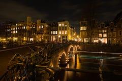 Nightscape med ljusa slingor av bilar och fartyg som korsar ovanför kanalerna av Amsterdam Arkivbilder