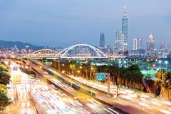 Nightscape of Taipei City with Taipei 101 Tower among skyscrapers in XinYi District downtown. Beautiful arch bridges & car trails on Dike Avenue ~ Riverside Royalty Free Stock Photography