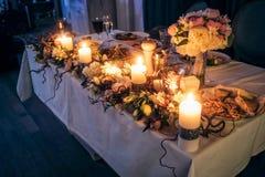 Nightscene与蜡烛的花装饰在婚礼桌上 免版税库存图片