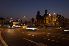 Nightscene in Barcelona. With vehicles on street with motion lights and old building behind Stock Photography