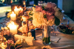 Nightscene flower decoration with candles on the wedding table. Nightscene flower decoration of white and pink peony  with lighting candles on the white served Stock Photo
