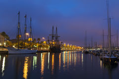 Nightscene with tall ships in harbour. Nightscene with a rigged schooner and tall sailing ships in a peaceful calm harbour with colourful city lights from the Royalty Free Stock Photo