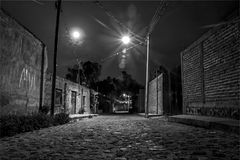 Nightshot bianco e nero spaventoso in vicolo vuoto in città messicana rurale durante la luna piena immagine stock