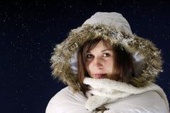 Nightshot de la mujer joven con el wintercoat contra s Fotografía de archivo libre de regalías