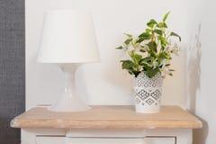 Nightstand con la lámpara y la planta Imagenes de archivo