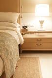 Nightstands bredvid hemtrevlig säng på natten fotografering för bildbyråer