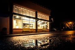 Nighttime снятый внешней витрины магазина родного города с отражениями в улице стоковые изображения rf