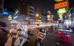Nighttime in Bangkok. A nighttime street scene in Bangkok, Thailand with cafe tables and motor bikes.  A blur of lights illustrates the traffic in the background Stock Photos