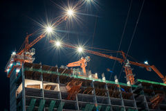 Nighttime with building and crane Stock Images