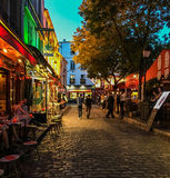 Nighttime on a busy Montmartre street on the Place du Tertre, Paris, France. Tourists stroll and diners lounge along a cobbled street on the Place du Tertre Stock Photos