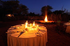 Nighttime campfire and table. Nighttime campfire and decorated table for outdoor safari catering royalty free stock image