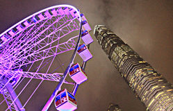 Nighttime Ferris Wheel and Skyscraper in Hong Kong. Stunning nighttime Ferris wheel and skyscraper in foggy Hong Kong stock photography