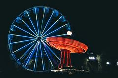 Nighttime with a Ferris Wheel and Swing. Light streaks of a Ferris Wheel and Swing rides at a carnival royalty free stock images