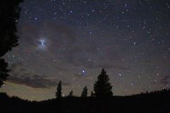 Nighttime photo of stars, trees, and mountains royalty free stock photo