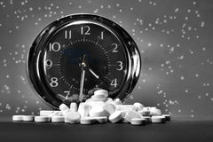 Nighttime Relief. Black and white image of a clock and a pile of pills against a starry background. Conceptual image to represent relief through the night (4 stock photos
