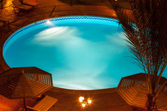 Nighttime setting of a luxury villa poolside. A nighttime view of a luxury villa poolside with umbrellas and tables Royalty Free Stock Photos