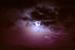 Nighttime sky with clouds and bright full moon with shiny. Stock Image