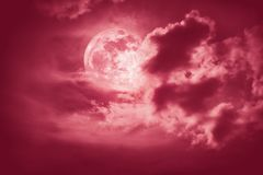 Nighttime sky with clouds and bright full moon with shiny. Attractive photo of cloudscape at nighttime. Night landscape of red sky with bright full moon behind royalty free stock image