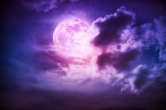 Nighttime sky with clouds and bright full moon with shiny. Attractive photo of cloudscape at nighttime. Night landscape of dark purple sky with bright full moon stock photo