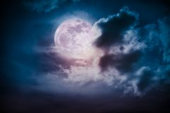 Nighttime sky with clouds and bright full moon with shiny. Attractive photo of cloudscape at nighttime. Night landscape of dark blue sky with bright full moon stock images