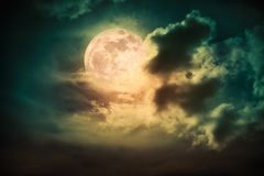 Nighttime sky with clouds and bright full moon with shiny. Attractive photo of cloudscape at nighttime. Night landscape of dark sky with bright full moon behind royalty free stock photography