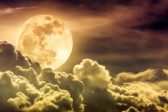 Nighttime sky with clouds and bright full moon with shiny. Attractive photo of gold background nighttime sky with clouds and bright full moon with shiny royalty free stock photography