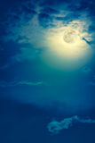Nighttime sky with clouds and bright full moon with shiny. Background of nighttime sky with cloud and full moon with shiny. Natural beauty at night with royalty free stock photo