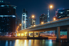 Nighttime skyline of Dubai with modern buildings, street lights and a bridge Stock Photos