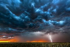Lightning storm over field in Roswell New Mexico. A nighttime, tornadic mezocyclone lightning storm shoots bolt of electricity to the ground and lights up the stock photo