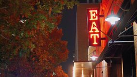 Night view of neon eat sign in city. A nighttime view of a red neon EAT sign on the side of a restaurant in a large city. Day/night matching available stock footage