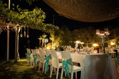 This nighttime wedding reception is garnished with blue and whit. Stunning wedding stock photography from Zakynthos Greece! A stunning summer wedding reception Royalty Free Stock Images