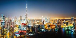 Nightttime horisont av en stor futuristisk stad vid natt Affärsfjärd, Dubai, Förenade Arabemiraten Arkivbild