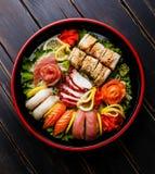 Nigiri, ρόλοι και sashimi σουσιών καθορισμένο σε Sushioke γύρω από το πιάτο Στοκ εικόνα με δικαίωμα ελεύθερης χρήσης